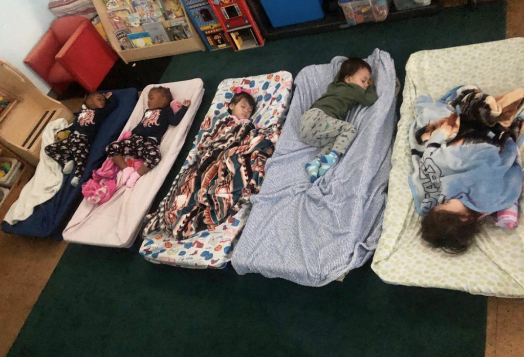 Five toddlers are lying on beds sleeping in The Learning Box Center nursery.