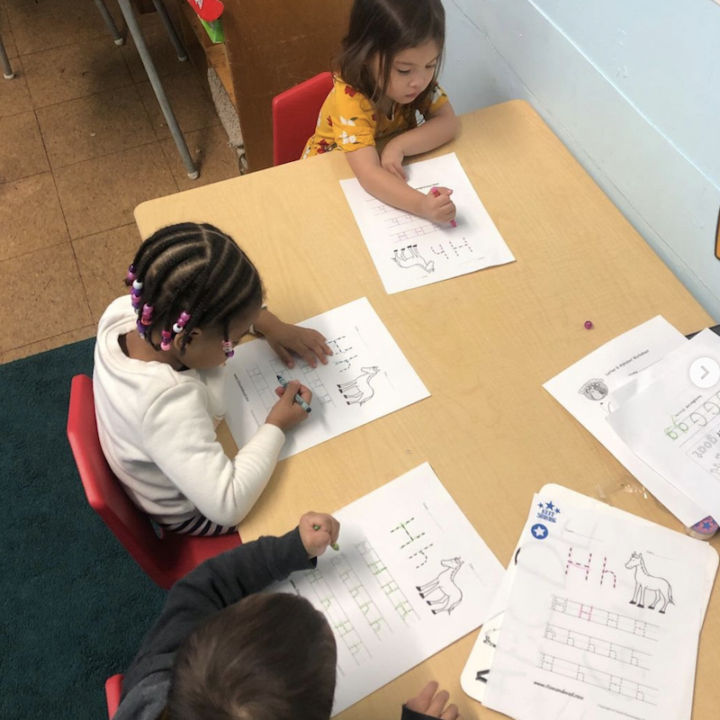 Children are sitting at a desk coloring to learn the alphabet.