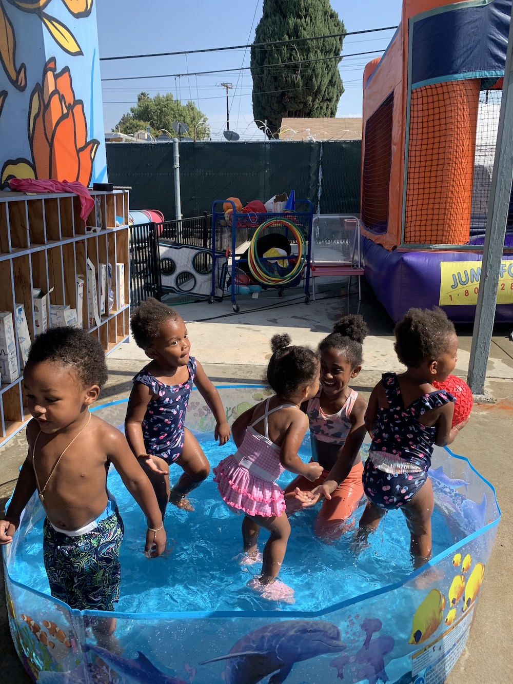 There are five toddlers in bathing suits playing in a kiddie pool.