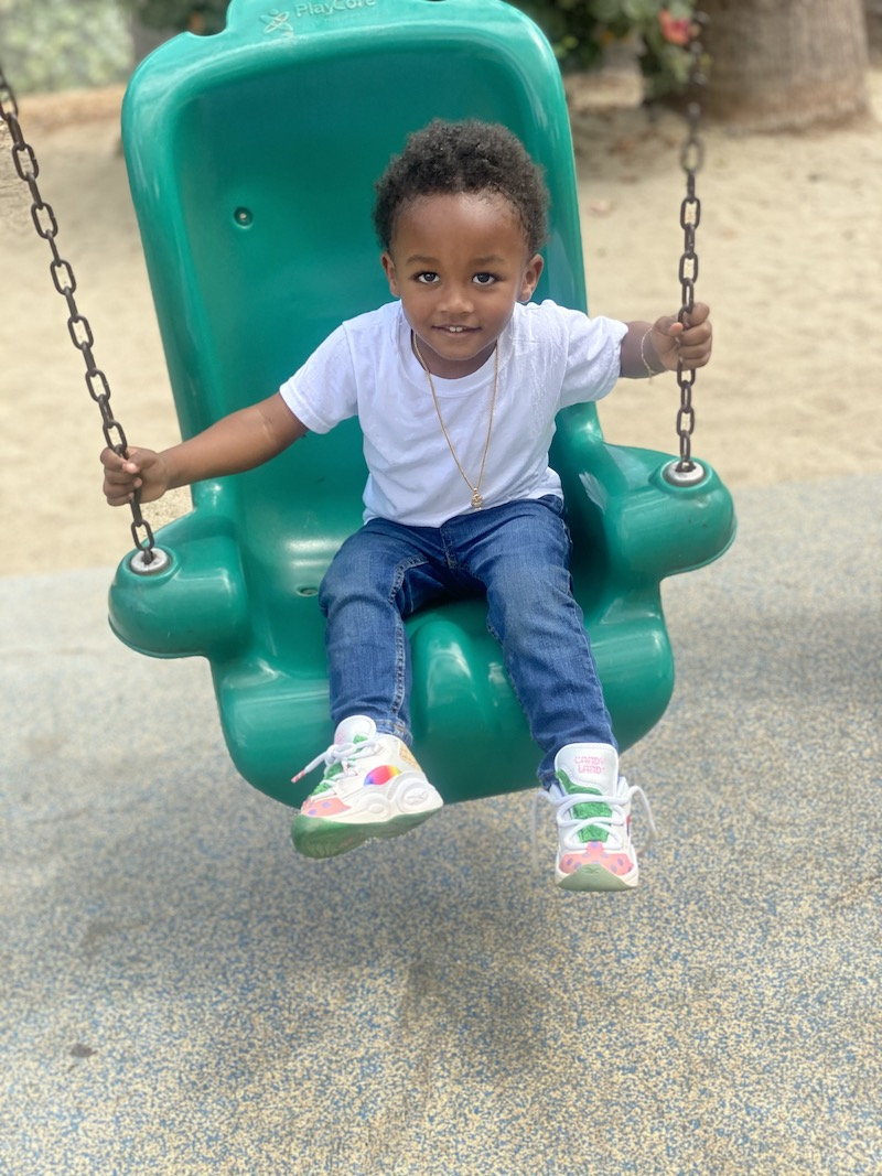 A toddler boy is happy swinging on a green swing at the playground.