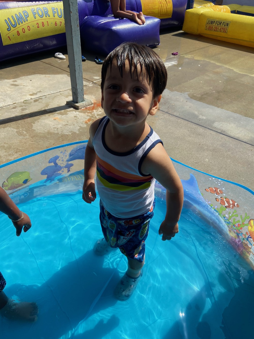 A little boy is smiling during play in a kiddie-sized pool.