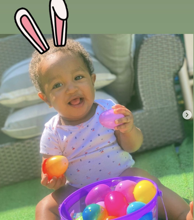 The baby girl sitting on the ground with a basket of Easter eggs has cartoon bunny ears on her head.