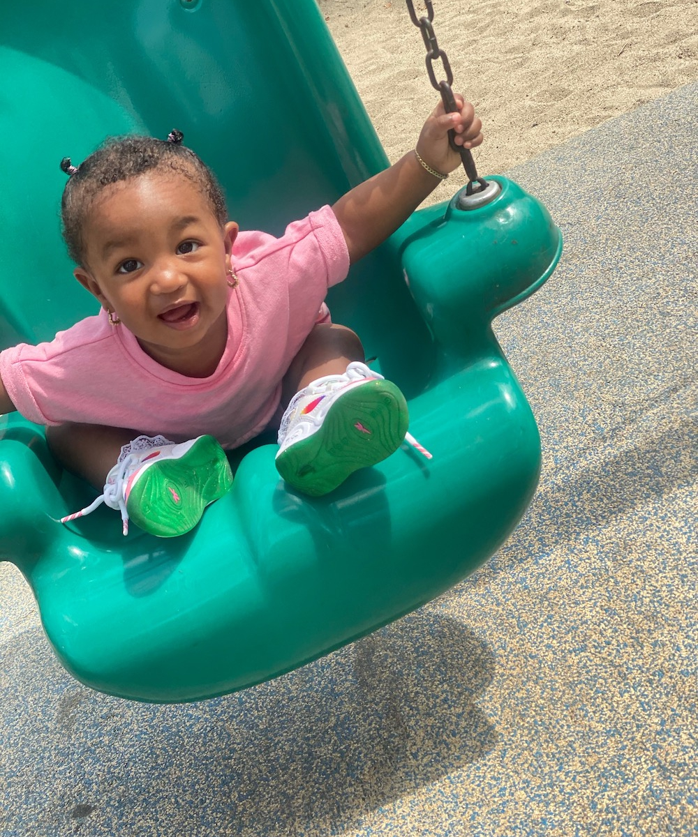 Toddler girl in a pink dress on a green swing at the park smiling for a picture.