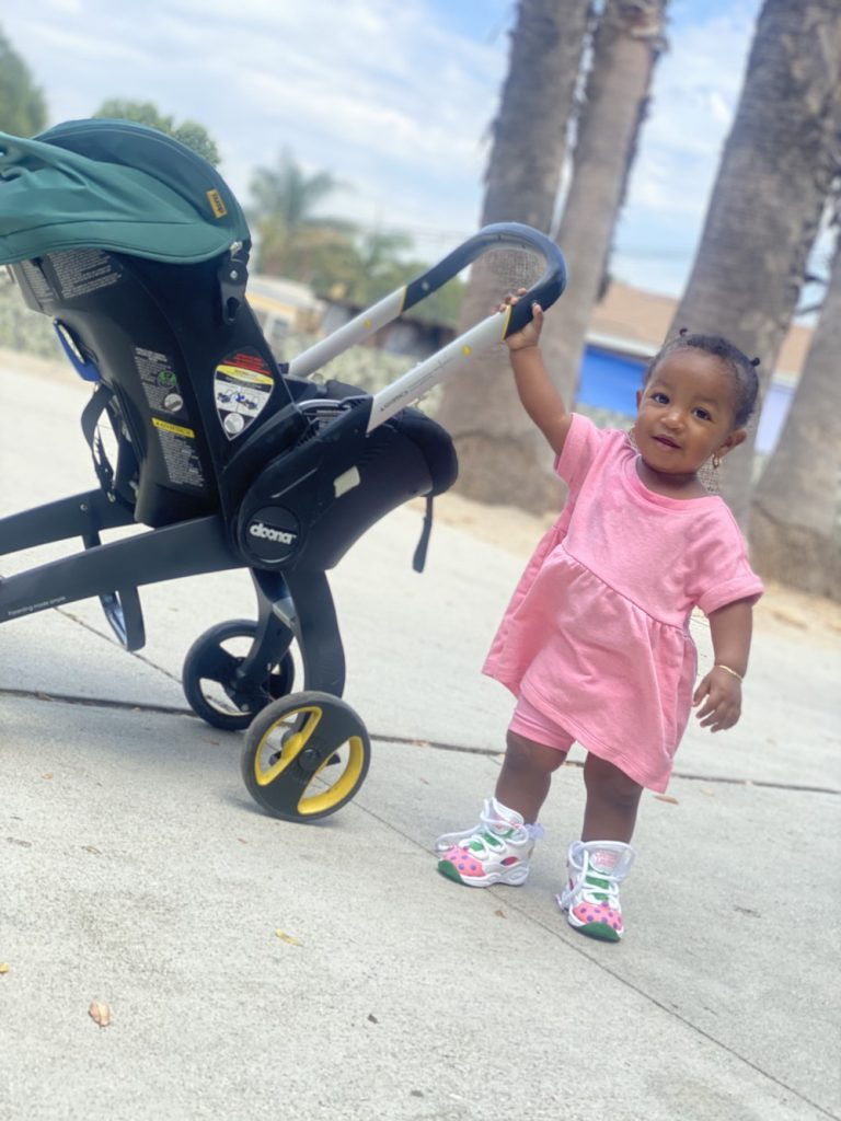 Baby girl wearing a pink dress holding on to her stroller walking in the park.