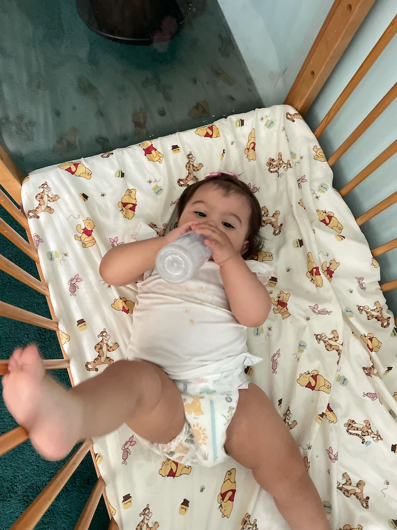 Baby girl drinking her bottle in a crib, ready for her nap.