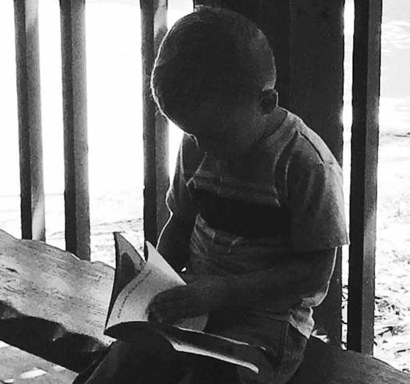 A black and white photo of a boy reading a book while sitting on a bench.