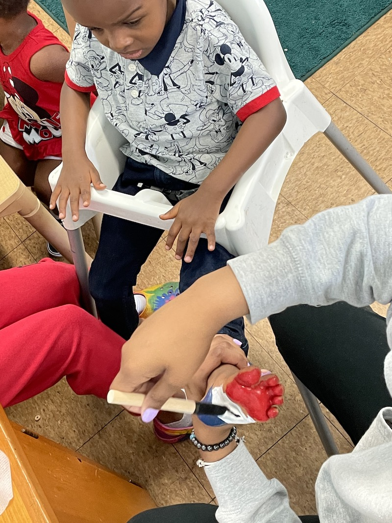 A teacher is painting a little boy's feet red, white, and blue for a craft project to take home to his parents for Fourth of July.