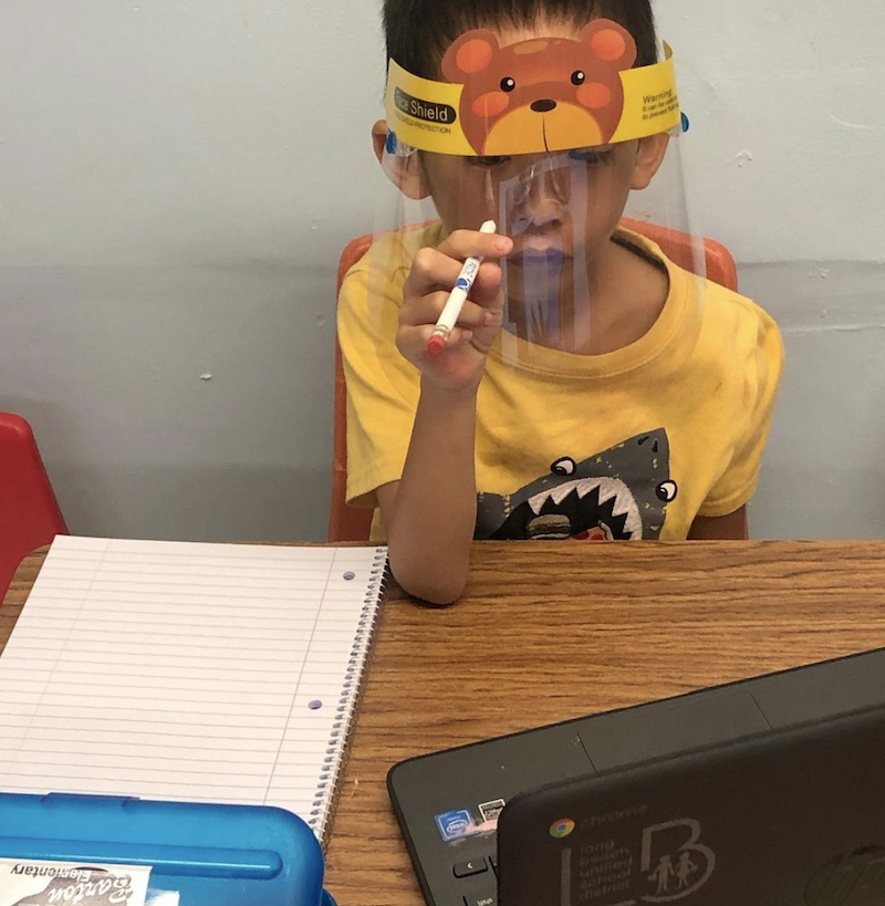 A little boy is sitting at a desk with a notepad wearing a yellow shirt and face mask, holding a pencil learning on his computer.