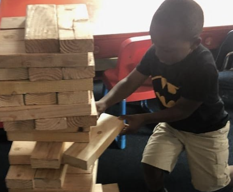 A boy is pulling a block from a super-sized Jenga block set.