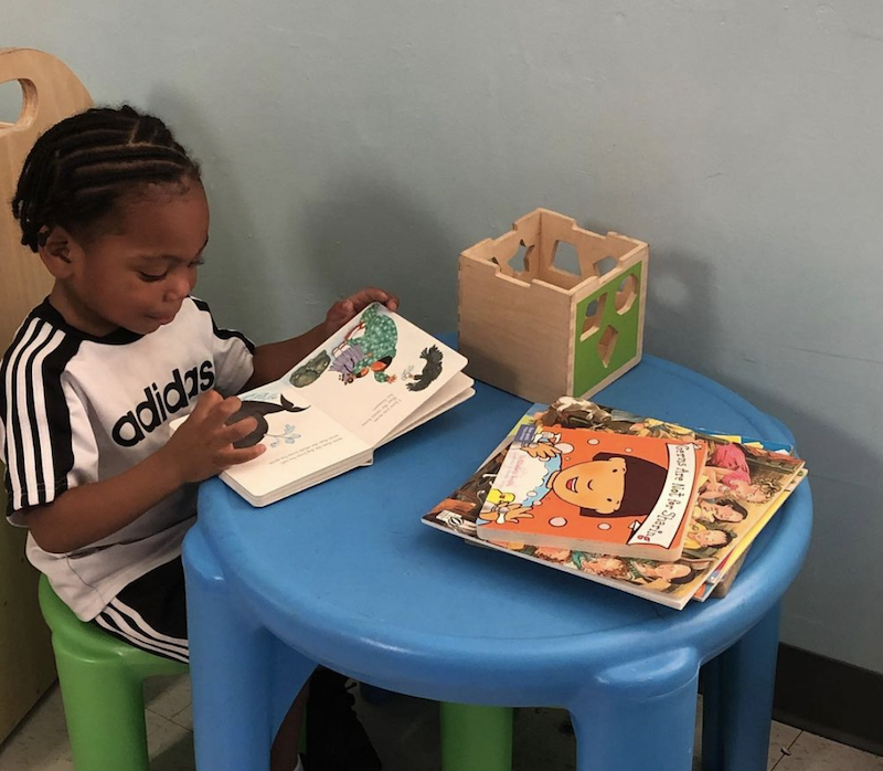 A little boy is reading a book sitting on a green chair at a blue desk.