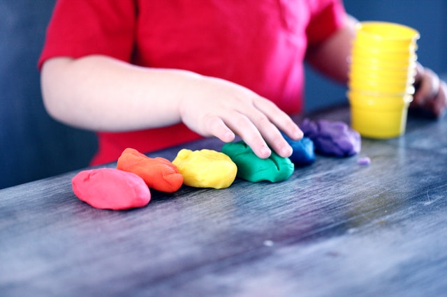A little boy is standing at a desk playing with Play-Doh.