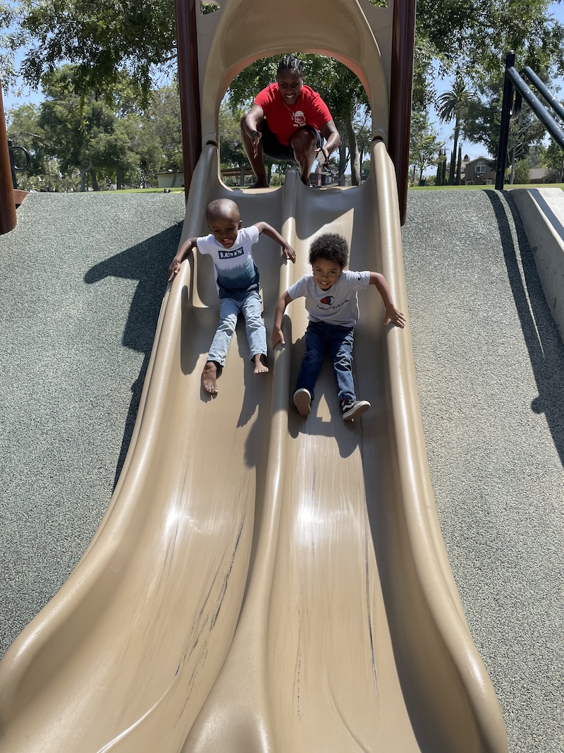 Two boys are sliding down the slide at the park with their teacher watching.