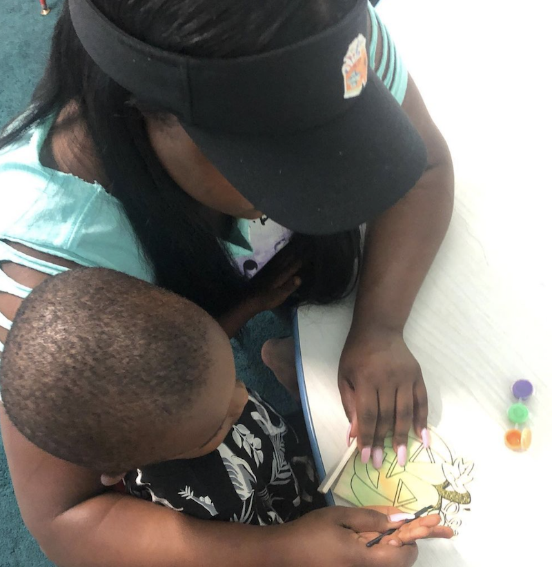 Teacher helping a child hold a paint brush to paint a Halloween picture.