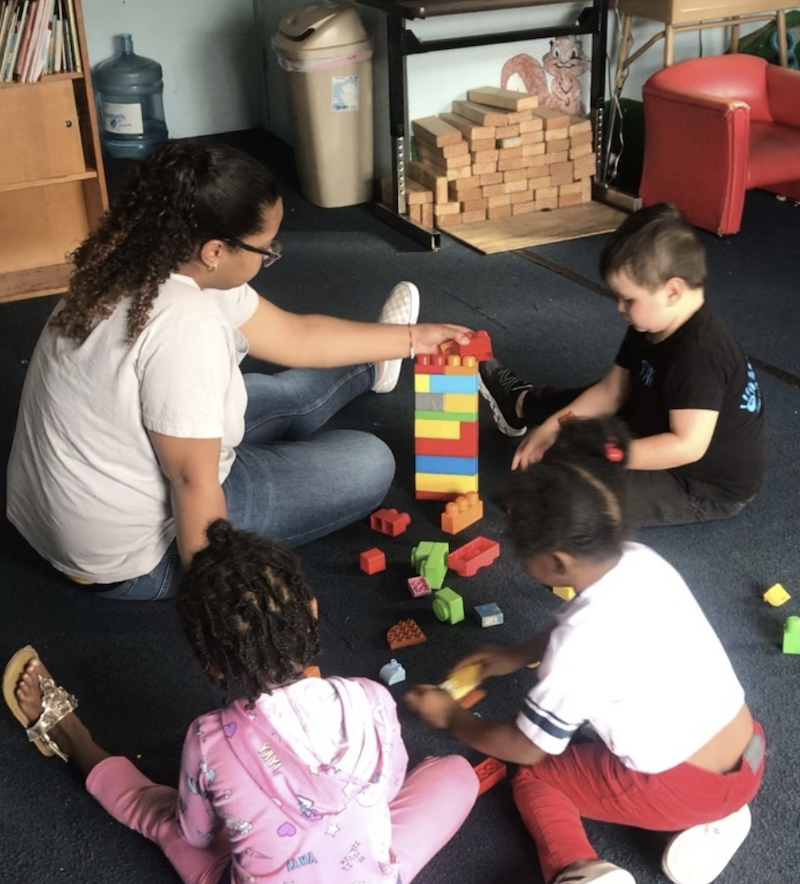The teacher and kids are playing with colored blocks on the floor of the playroom.