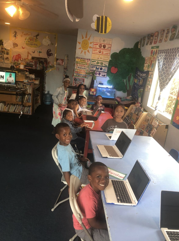 A teacher is smiling with kids for a picture while learning on their computers.