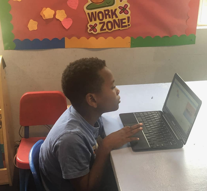 A boy is sitting at a desk learning on a computer.
