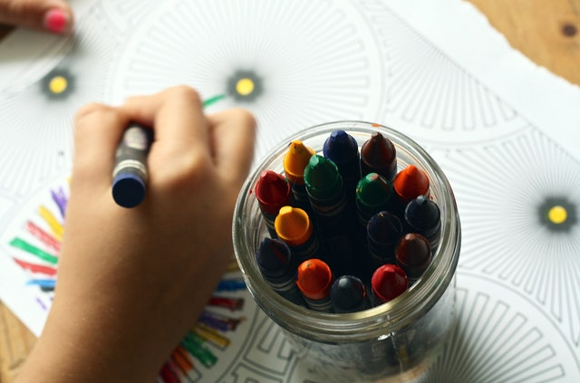 A child is coloring in a coloring book using Crayons.