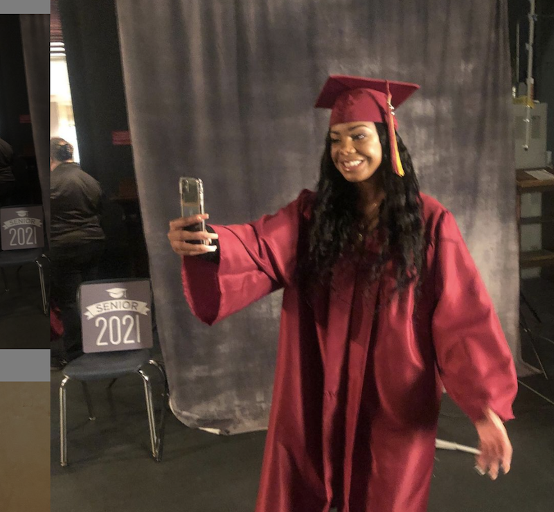 Mia is taking a selfie in her graduation gown at her graduation.