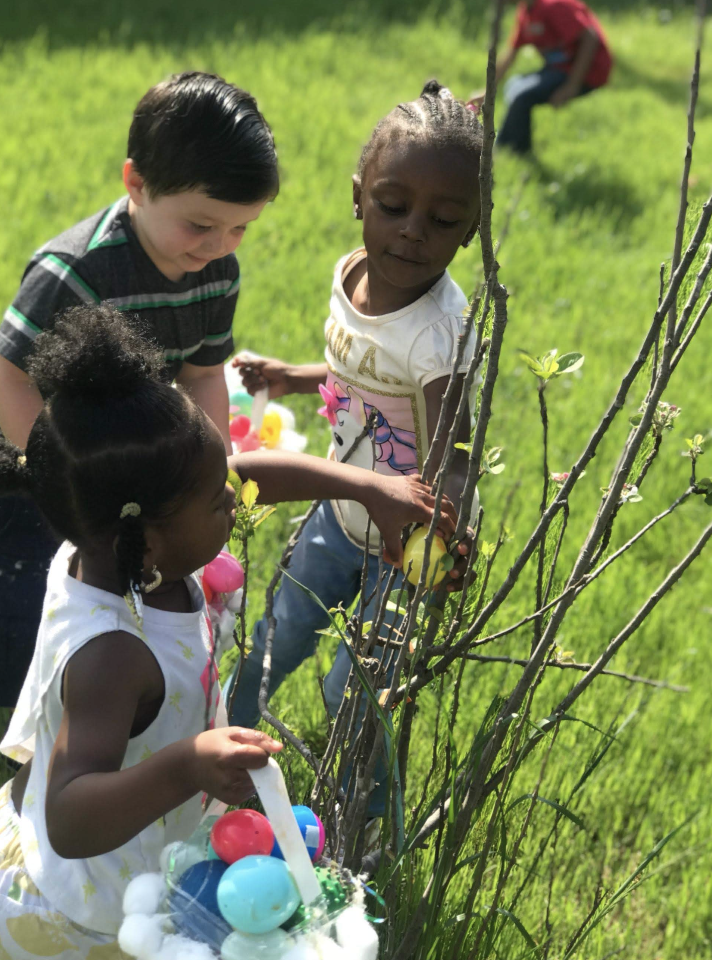 The little girl helping another get an easter egg from a tree while a boy watches.