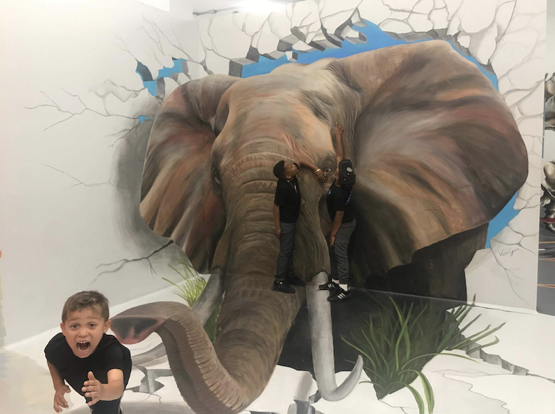 A boy is standing in front of a painted elephant at the museum, being silly by acting like he is reaching out for help.
