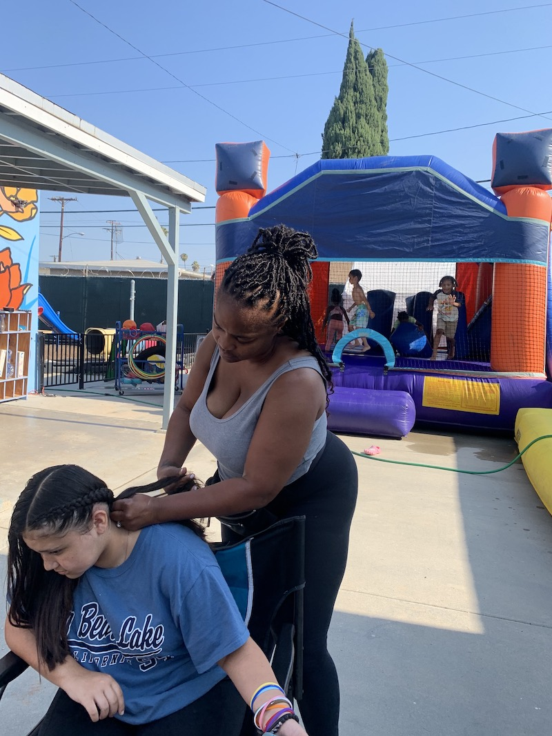 Ms. Tee is braiding hair on the playground at The Learning Center.