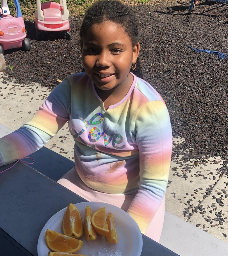 A girl is wearing a rainbow-colored shirt eating oranges.