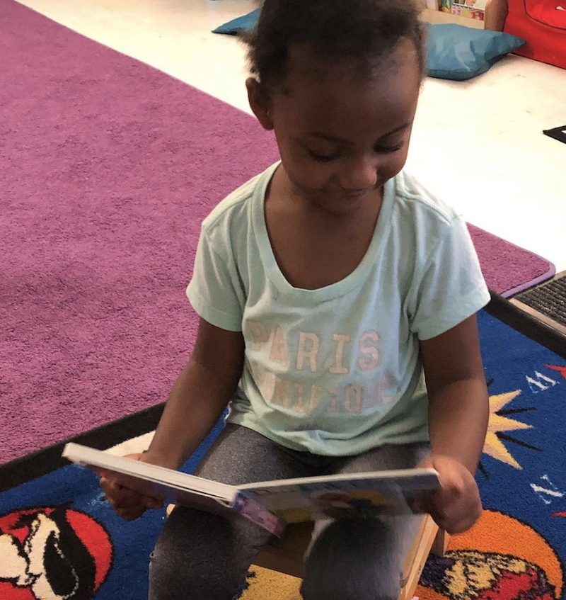 A little girl is sitting in the library reading a book at The Learning Box.