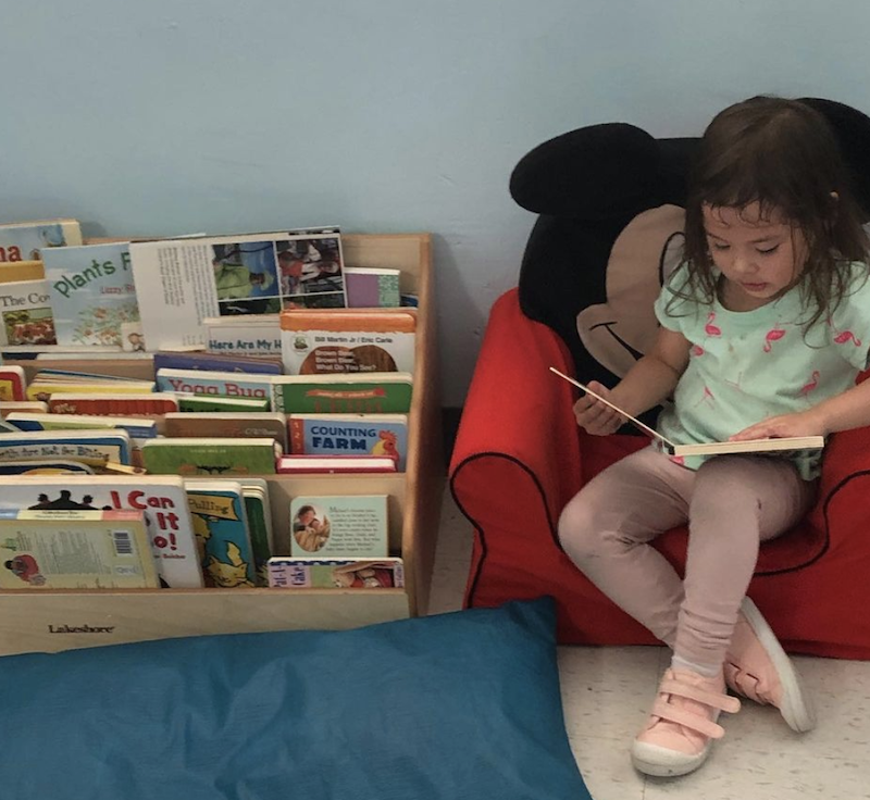 A little girl is sitting in a Mickey Mouse chair, reading a book and a rack of books beside her.