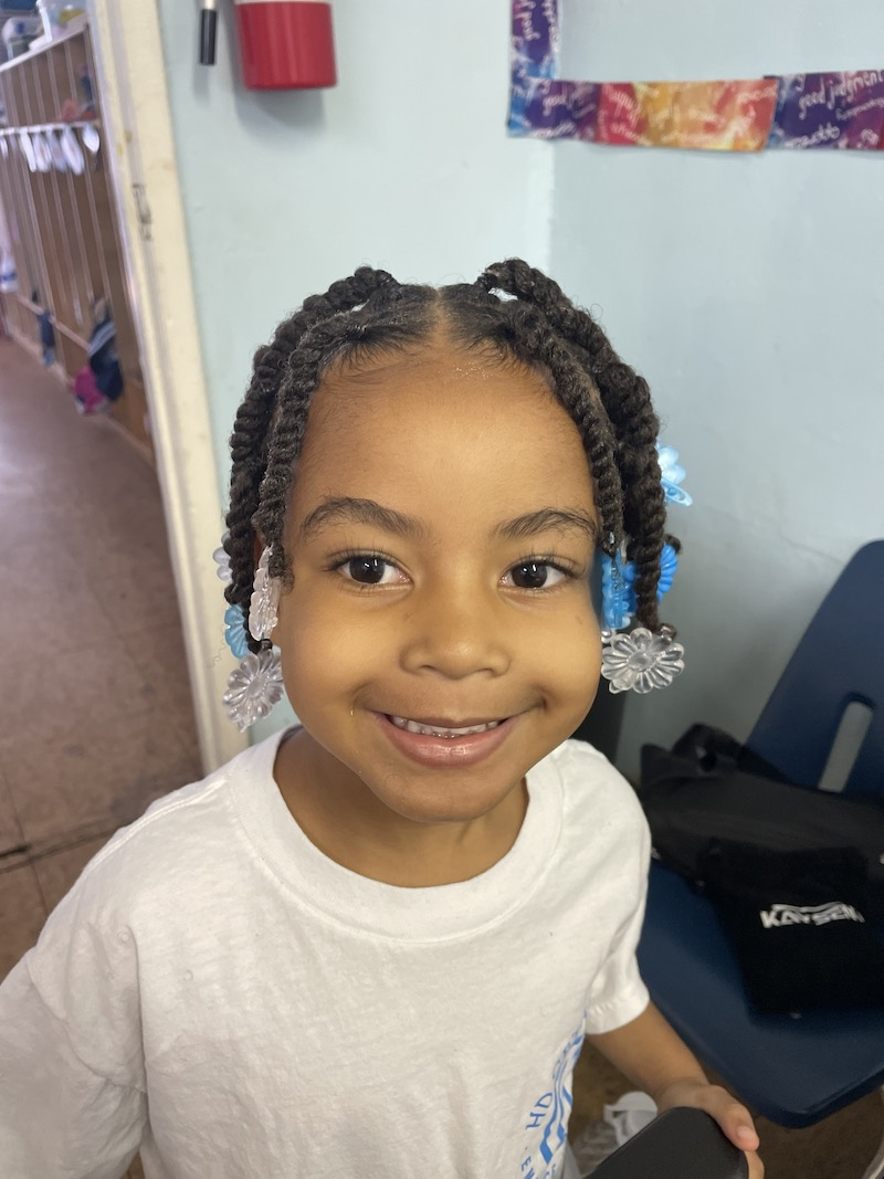 A little girl is smiling after she got her hair braided.