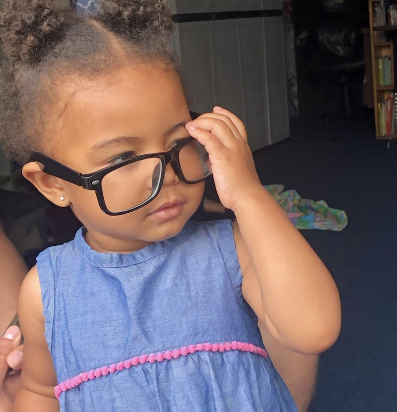A little girl is posing for the camera, taking off her glasses after playing.