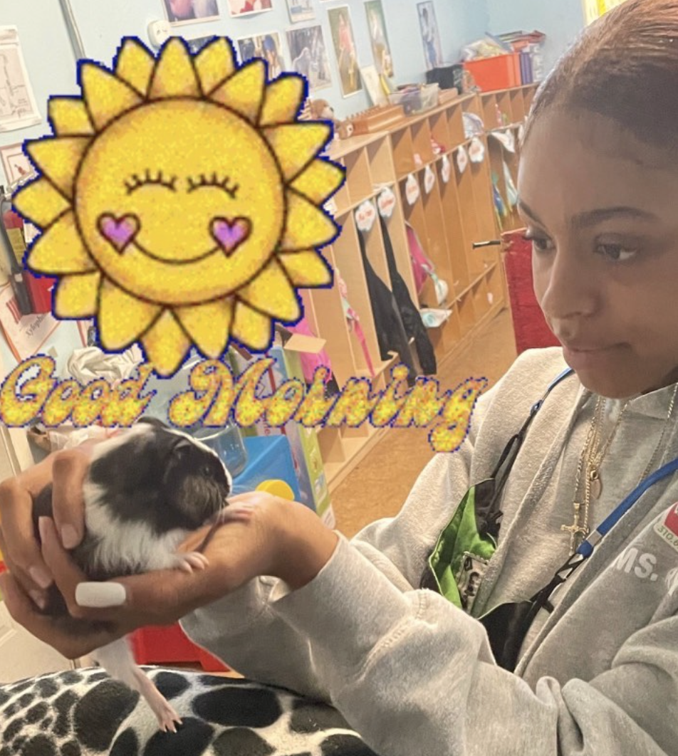 Mia is holding the newest pet, a guinea pig, in the playroom at The Learning Box.