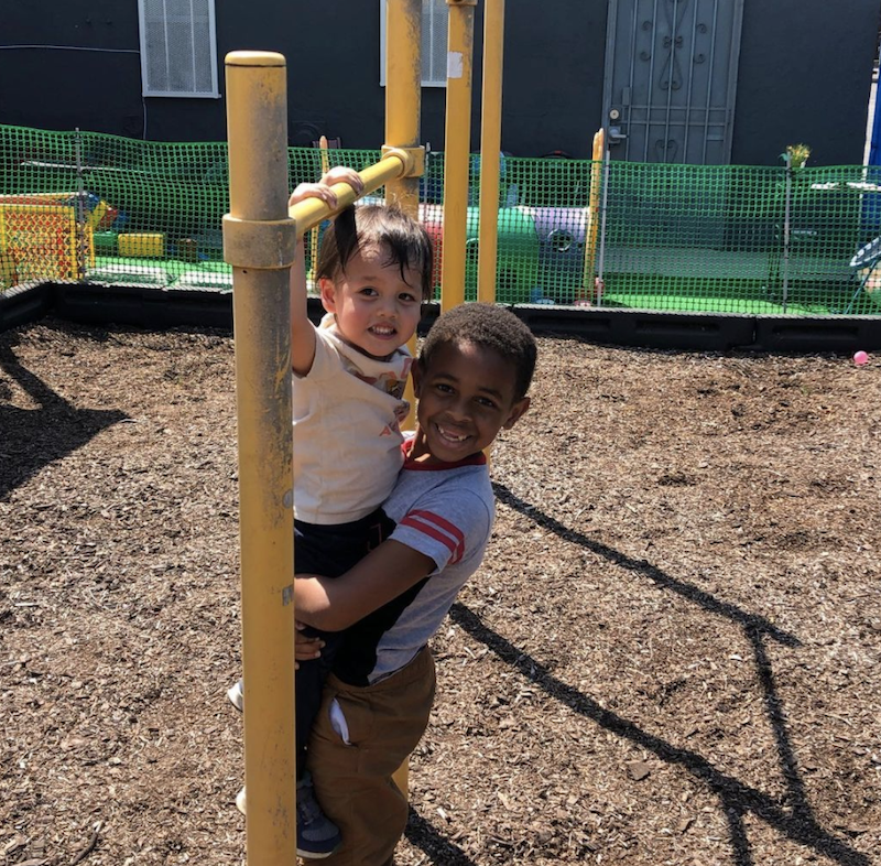 A little boy is holding another so he can reach the bar at the jungle gym.
