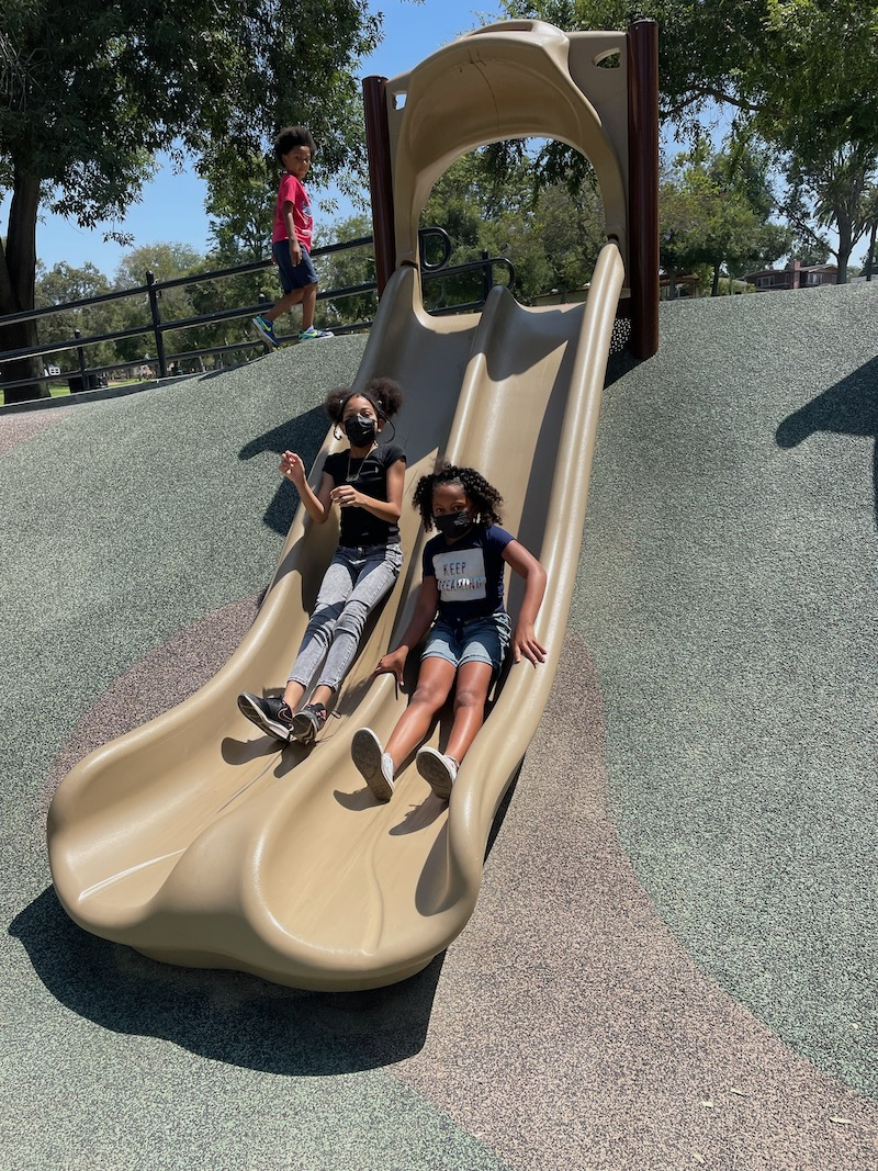 Two girls on the slide are having fun at the park.