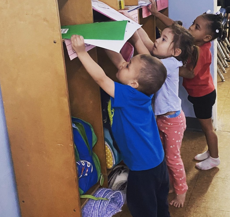 Three kids are holding their school supplies, putting them away in their cubbies until the next lesson.