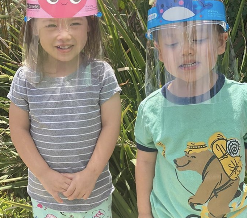 Girl and boy are wearing face shields to be safe from Covid are posing for a picture.