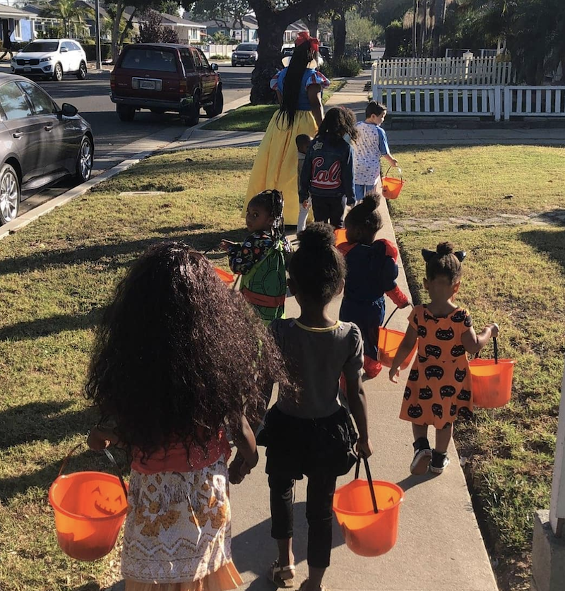 Children are dressed up in costumes for Halloween carrying candy baskets.