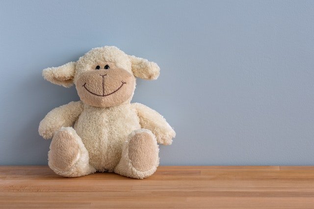 A lamb stuffed animal sitting on a desk with a blue background.