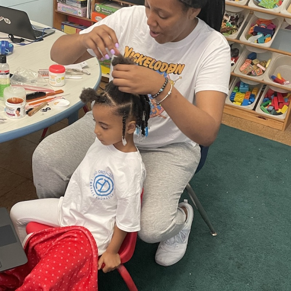 A little girl is sitting on a chair in the playroom while her teacher braids her hair.