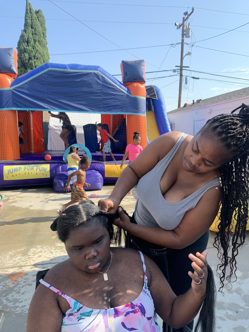 Ms. Tee is braiding a girl's hair while children play in a bounce house in the background.
