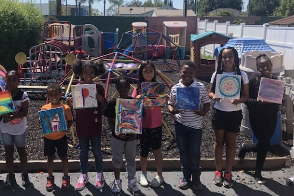 Proud children are smiling, holding up their painting, and taking a picture.