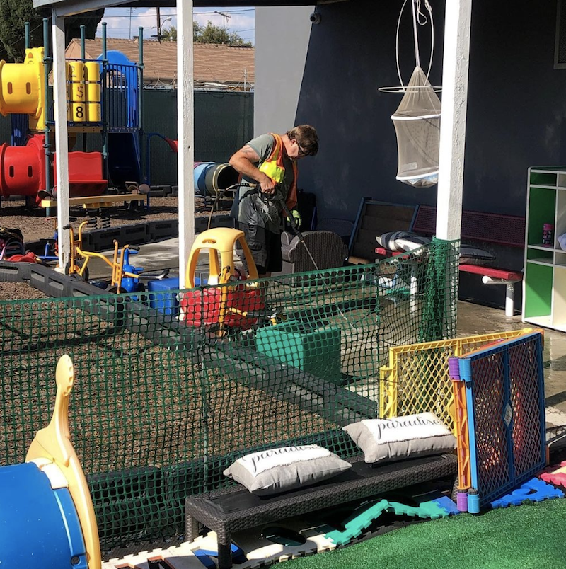 A construction worker is fixing the concrete at The Learning Box playground to be safe and clean.