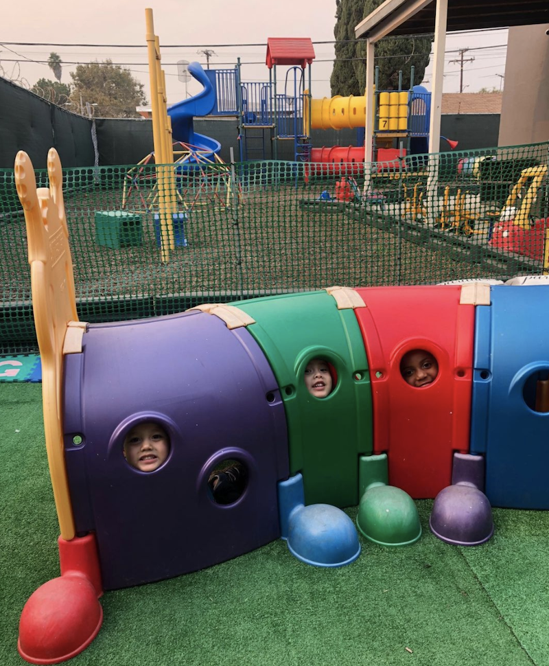 Three kids are smiling while looking out of the Climb-N-Crawl Caterpillar outdoor play structure peepholes on The Learning Box playground.