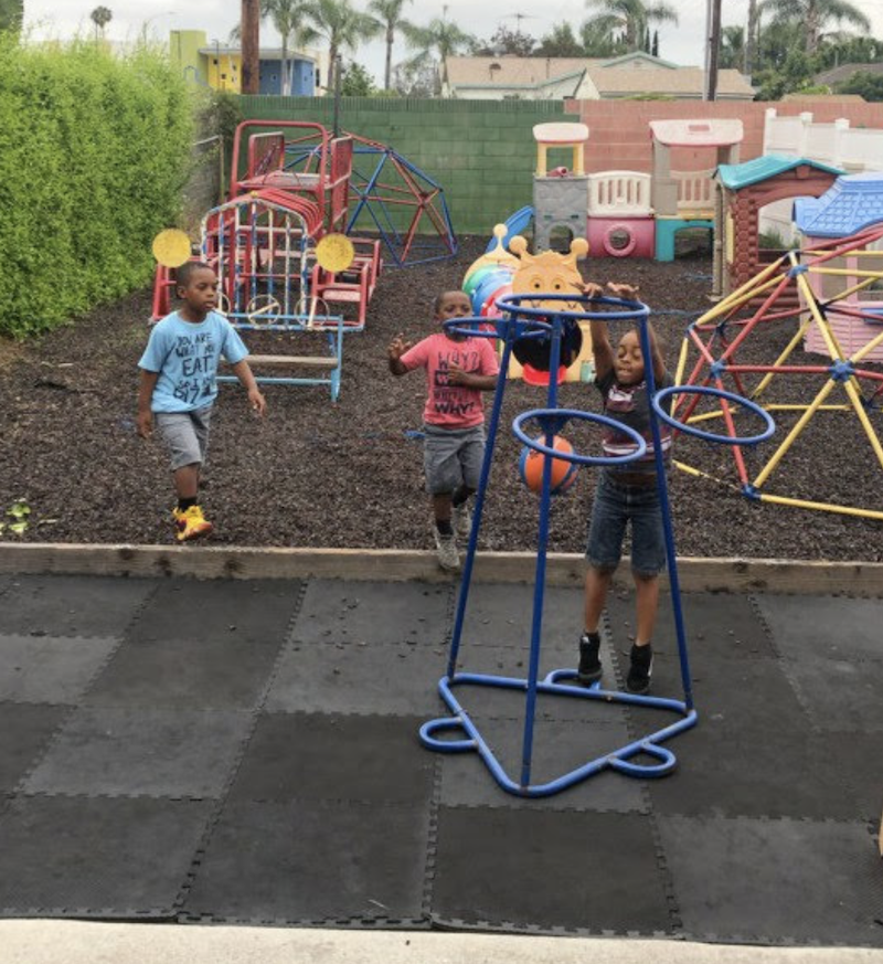 Kids are shooting the basketball in the hoop on The Learning Box playground.