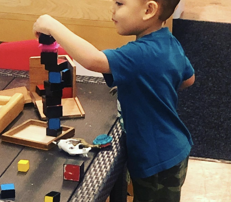 A boy is standing by a table playing with building blocks.