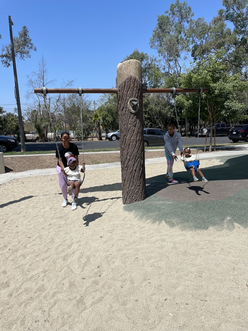 Two children are on the swing set with their teachers pushing them.