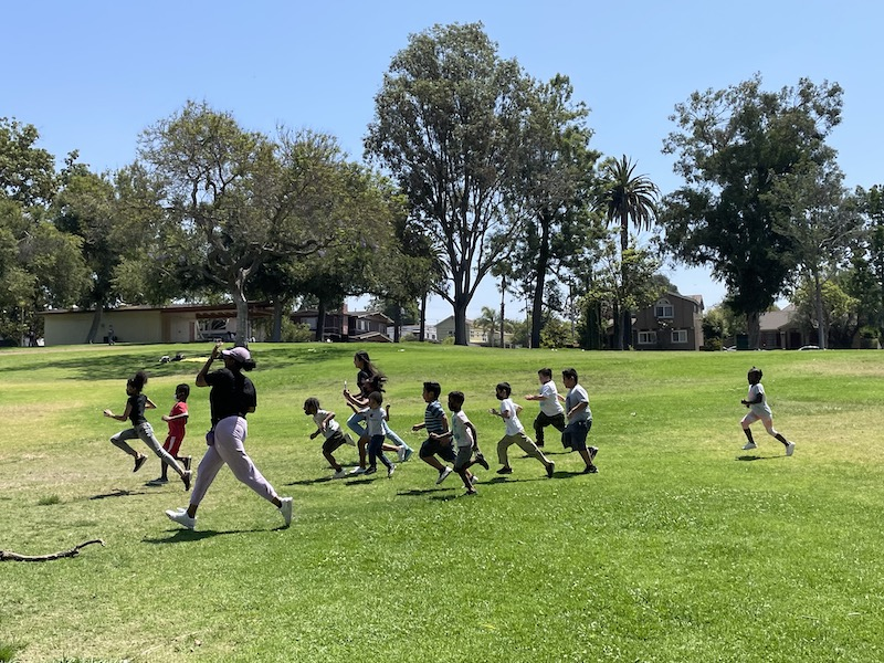 Children of The Learning Center are running through the park.