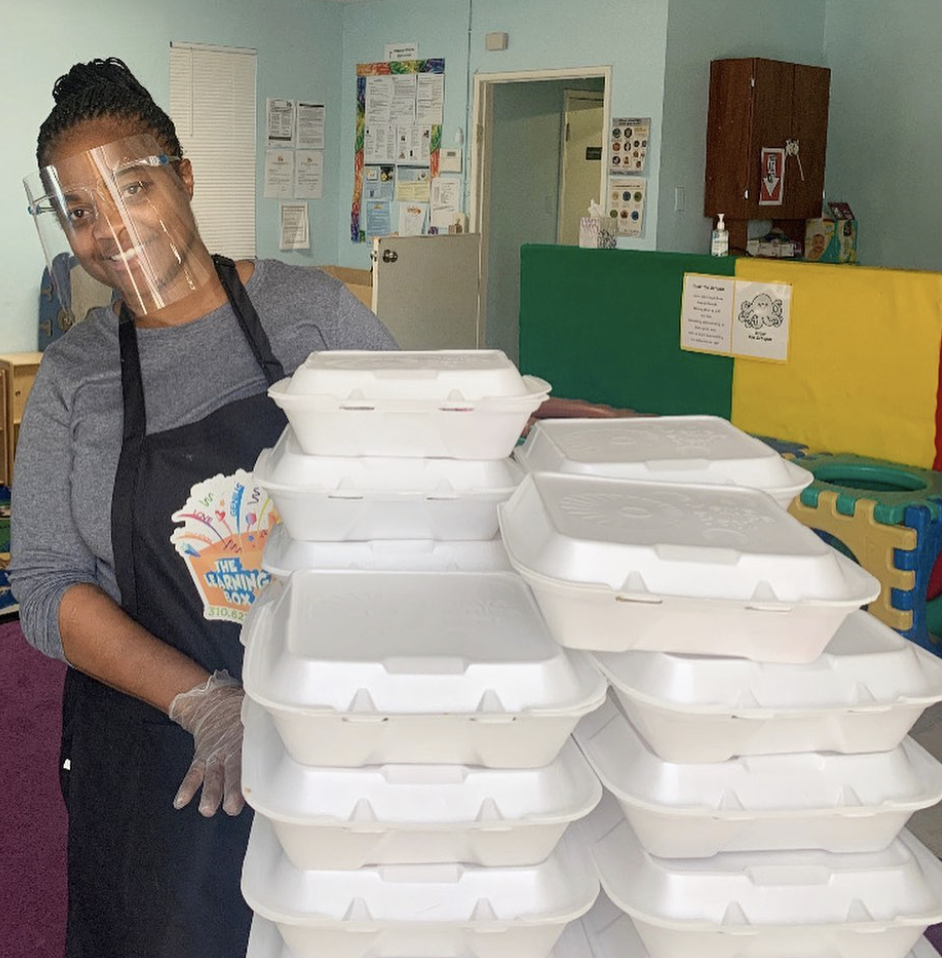 Ms. Tee is standing behind lunch boxes that will be feed to the children.