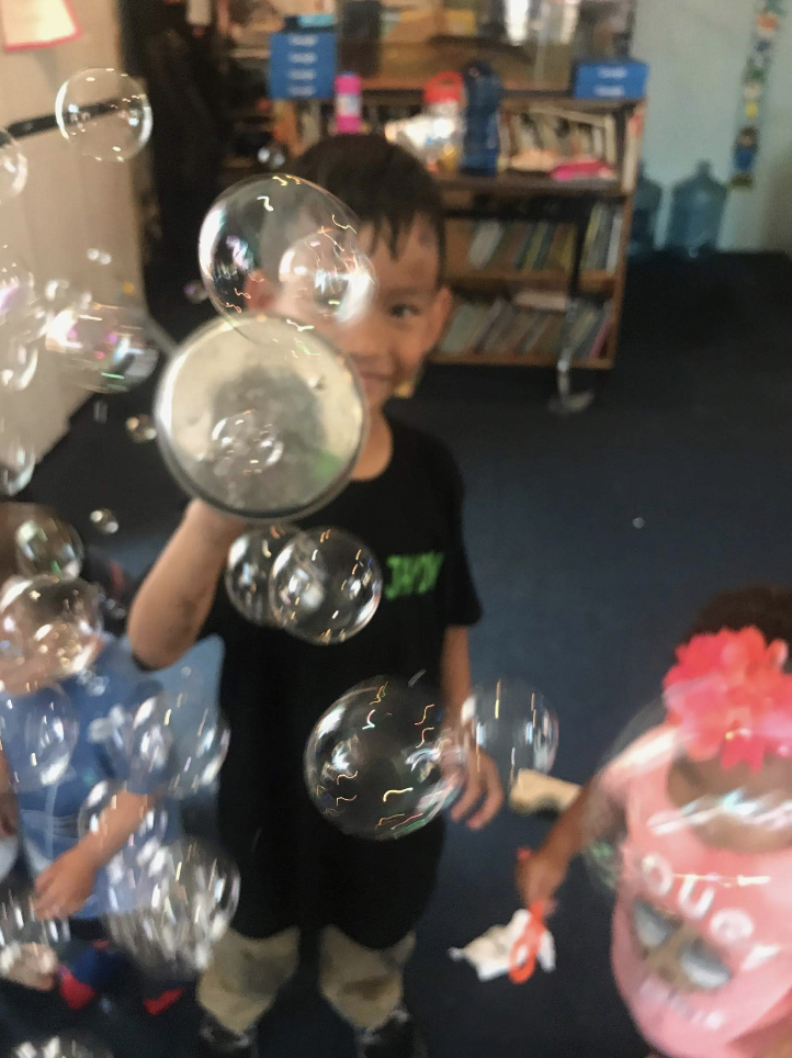 Smiling kids are blowing bubbles and popping them.