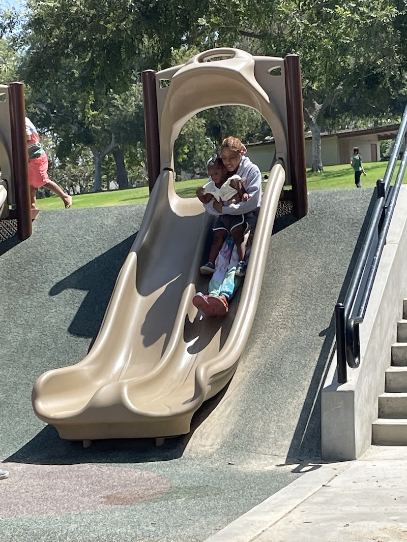 A little girl is being held by her teacher, sliding down the slide.