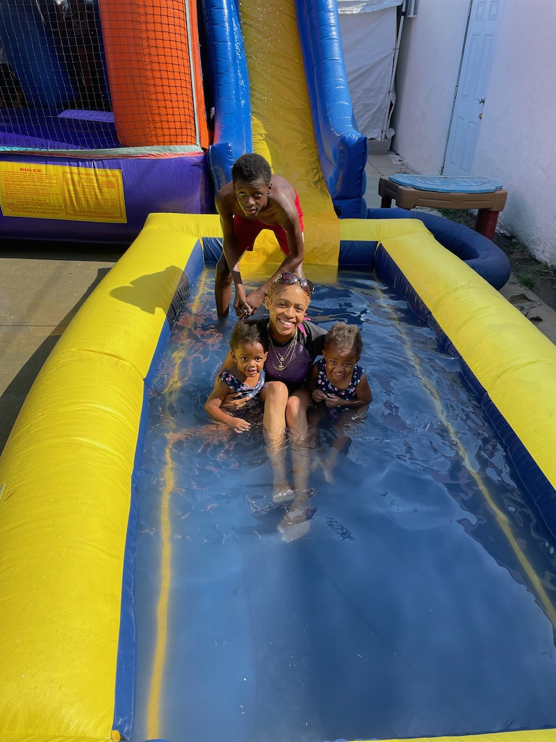 The teacher holds two children, and a boy is standing behind them in the pool, smiling while taking a picture.
